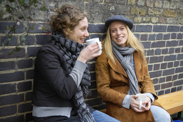 Two women having a coffee outdoors.