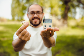 Key, House, Human Hand on a background of green grass