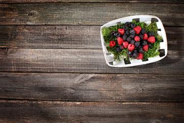 berries raspberries and blackberries in a basket on a wooden bac