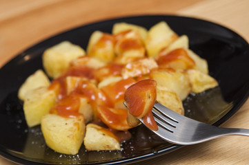 "Spanish food: delicious ""patatas bravas"", hot and spicy potatoes."