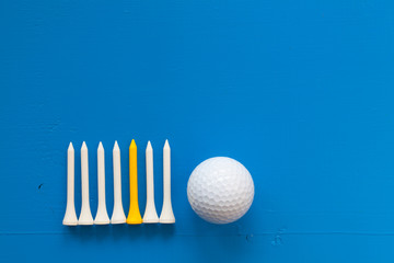 Golf ball and wooden golf tees on the blue desk