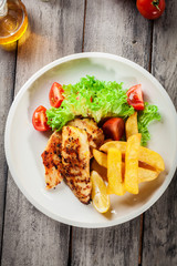 Grilled chicken breasts served with fries and fresh salad
