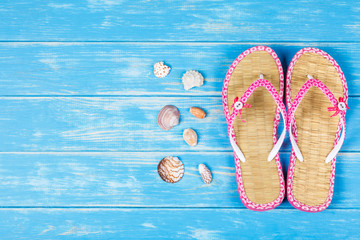 View of seashells and flip-flops lying on blue wooden background