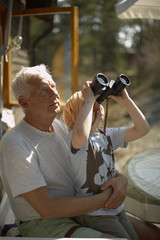 Grandfather with grandson looking through a pair of binoculars.