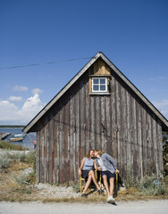 A couple kissing in front of a shed.
