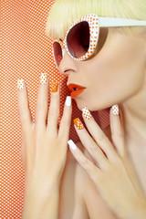 Wall Mural - Солнечно оранжевый маникюр с точками на женских ногтях  и макияж крупным планом в солнечных очках.