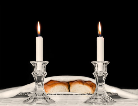Shabbat candles in glass candlesticks with blurred challah background