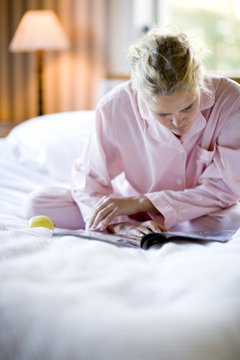 A woman sitting in a bed reading a paper.