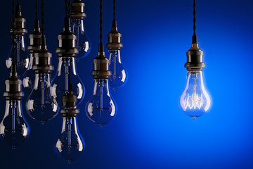 Decorative antique Edison style light bulbs against a blue background. 3d render