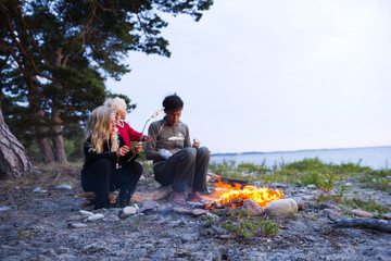 A Scandinavian woman and two girls sitting by a camp fire, Oland, Sweden.