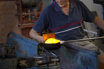 Glass blower in a glasswork.