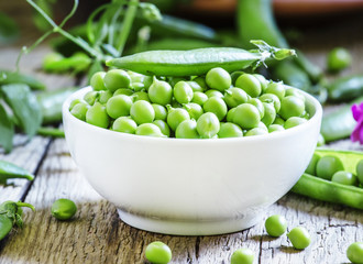 Peeled pea green peas in a white porcelain bowl, vintage wooden