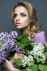 Beautiful girl in a purple dress and a bouquet of lilacs. The model is in an image of spring. The photo was taken in a studio