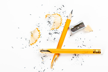 Broken pencil with metal sharpener and shavings.