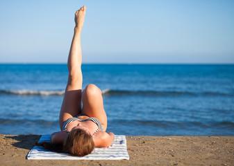 Woman on the beach during summer vacation enjoying hot sun