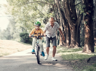 Father help his son learn to ride bicycle