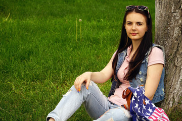 young beautiful woman sitting near a tree on the grass