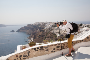 The photographer takes a photo beautiful landscape of Santorini, Greece. Shooting. Camera. Photographer. Shoot video.