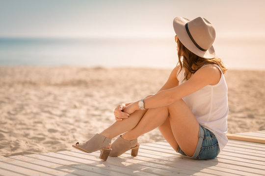 Stylish woman at the summer beach in a hot day
