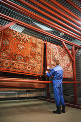 The employee corrects the Laundry hanging in the drying room, the rugs at the cleaners