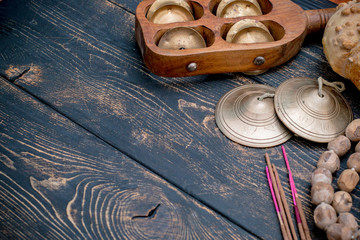 Ethnic musical instruments of India on the old wooden black scratched background. Wooden beads, incense sticks, sandalwood.