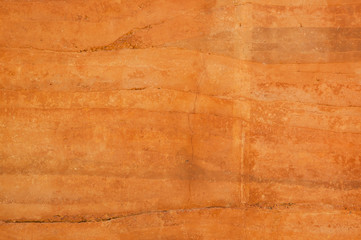 Rammed earth wall with different shades of orange soil