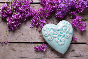 Violet lilac flowers and  turquoise decorative heart on aged  wo
