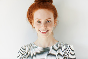 Close up view of attractive happy Caucasian woman with ginger hair and freckles wearing stylish clothes looking and smiling at the camera posing against white studio wall. Youth and happiness concept
