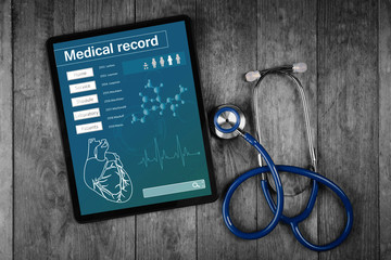 Medical record on tablet screen with stethoscope on wooden background