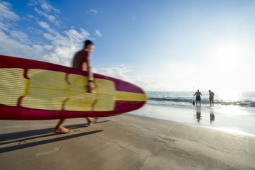 Motion blur of young Brazilian man carrying a stand up paddle longboard surfboard on the shore of Copacabana Beach in Rio de Janeiro, Brazil