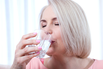 Portrait beautiful middle aged woman drinking water in the morning