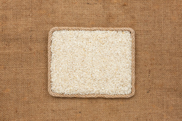 Frame made of rope with rice grains on sackcloth, view from above