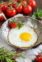 Fried egg with tomatoes and herbs n a old frying pan