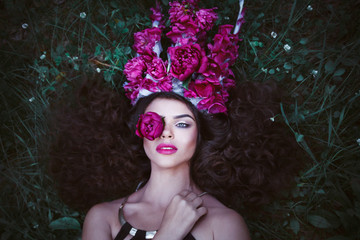 Beautiful woman with crown from purple peonies