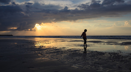 boy have fun on the sandy beach on sunset