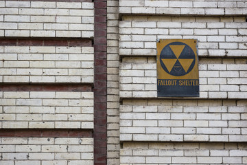 Old cold war fallout shelter sign on brick wall