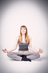 Young and sporty girl training. Yoga exercise on gray background