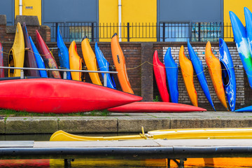 Row of colourful kayaks leaning against brick wall on the Regent's canal in London