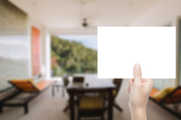 hand holding blank paper with interior background