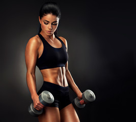 Beautiful fitness woman lifting dumbbells . Fitness sporty woman showing her well trained body . A beautiful girl's body with rippling muscles from strength training .