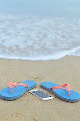 Top view close up on mobile phone with slippers on summer beach background. Happy joyful vacation