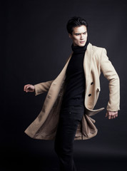 cool real young man in coat on black background posing