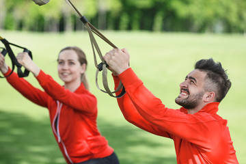 Portrait of sport man and woman training with help of suspension trainer in green park or forest on fresh air. His fitness partner on background.