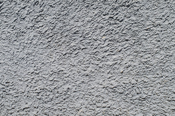 Grey rough plaster, concrete on wall closeup in sunny day, background, texture series