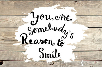 You are somebody's reason to smile hand lettering text on wooden background