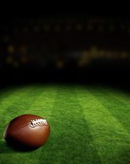 American football on green field stadium at night