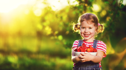 happy laughing child girl with ripe strawberry in summer on natu