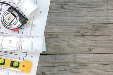 contractor work tools with floor plan on wooden desk