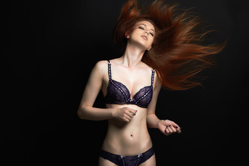 Sexy young red hair woman in underwear on dark background.beautiful girl in lingerie