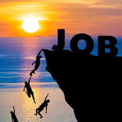 Silhouette of people climbs into cliff to reach the word JOB with sunrise (find job recruitment concept)